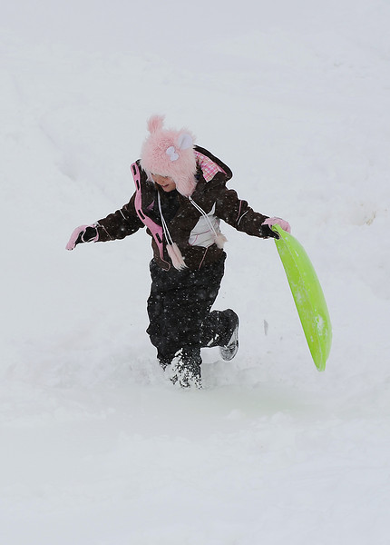 Haven Encineas, 8, sports a fuzzy teddy bear hat as she makes her way back up the sledding hill Friday.