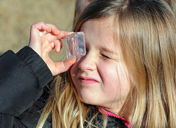 Carli Howell, 7, looks through the magnifying lens part of a bug box Wednesday after looking for bugs outside Lincoln Elementary School in Loveland with classmates. Rangers from Rocky Mountain National Park visited the school to teach kids about invertebrates and insects. Photo by Jenny Sparks