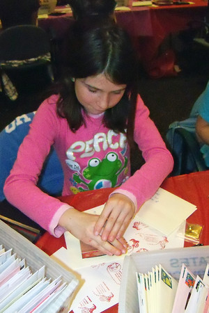 Emily LeGay, 10, practices using a hand-stamp cachet Saturday at a stamp camp before trying out the real thing on valentines sent through LovelandÕs Valentine Remailing Program.