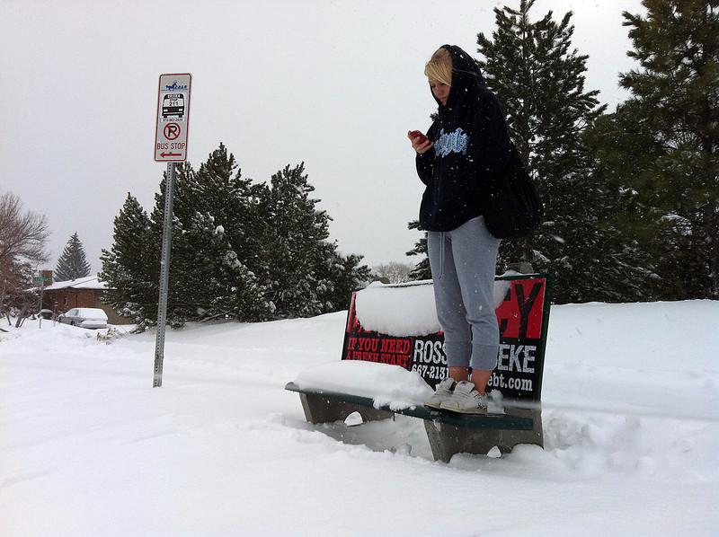 Kaeley Cook, 16, stands on a bench while waiting for a bus Friday morning at the corner of Estrella Avenue and West 22nd Street in Loveland. The Loveland High School sophmore was trying to get to a friend's house after school was cancelled.
