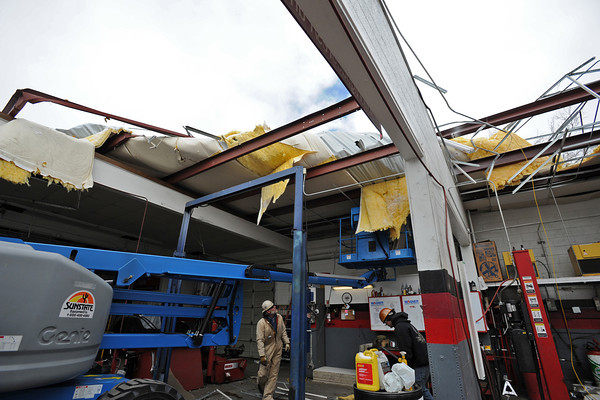 Todd Katnig, left, Justin Pecor, right, and Brandon Hummel, on lift, with Metal Solutions, work Thursday afternoon at Big O Tires in Loveland after wind blew part of the roof off the building. Photo by Jenny Sparks