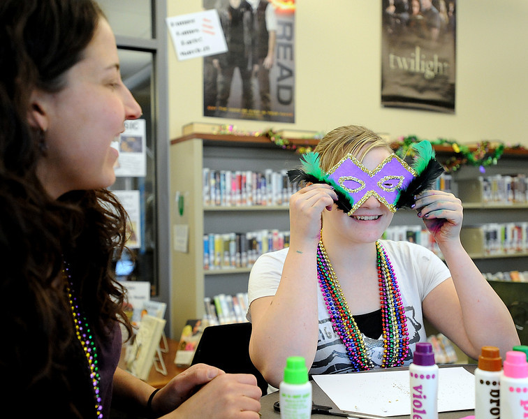 Danielle Carr, 14, laughs as she tries to peek through a tiny eye hole on the Mardi Gras mask she made Tuesday as teen librarian Michelle Turner also laughs during the  Teen Mardi Gras Fun party at the Loveland Public Library. Photo by Jenny Sparks