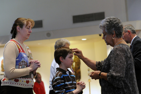 Mary Westerfield, left, waits in line while her son Paul, 7, receives the distribution of the ashes from Mary Berndt during an Ash Wednesday mass on Wednesday at St. John the Evangelist Catholic Church, 1730 W. 12th St. in Loveland.