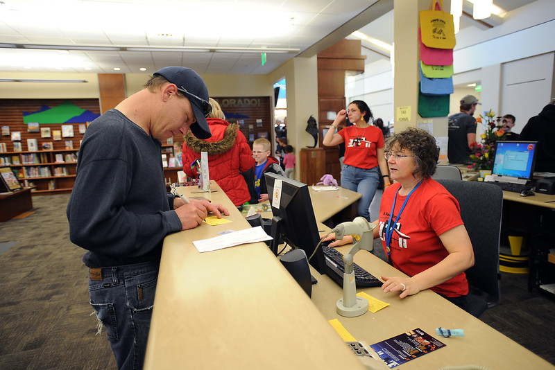 Jason Crane, left, is assisted by Loveland Public Library circulation aide Darlene Oliver as he applies for a new library card at the customer service area on Saturday, Feb. 18, 2012.