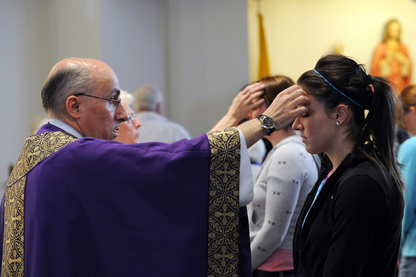 The Rev. Jose Maria Quera, left, places ashes on Andrea Baumann's forehead during an Ash Wednesday mass at St. John the Evangelist Catholic Church on Wednesday.