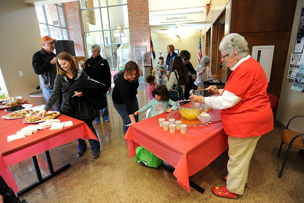 Loveland Public Library trainer and special projects librarian Sue Baccari, right, fills a cup with punch to give out to visitors during the library's grand reopening ceremony Saturday, Feb. 18, 2012.