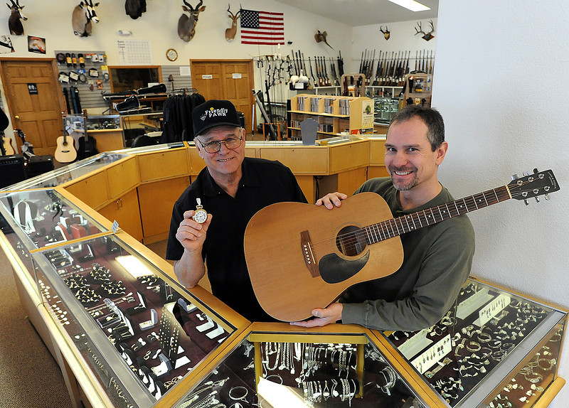Ray Steele, left, and Ray Steele Jr., owners of Friendly Pawn in downtown Loveland, pose for a photo Monday holding some of the items they sell in front of their jewelry counter. They say they look forward to City Council approval of an ordinance requiring pawn shop licenses in Loveland. Photo by Jenny Sparks