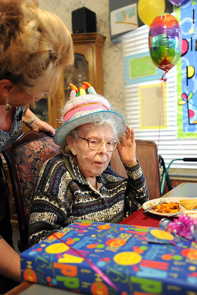 Regina Elmshaeuser adjusts her birthday hat as Trisha Campbell, marketing director at The Courtyard, chats with her Monday during a birthday party to celebrate turning 100 years old at the Courtyard in Loveland. Photo by Jenny Sparks