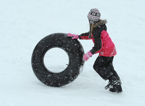 Isabella Romero, 8, rolls her innertube back up the sledding hill Friday in Loveland.