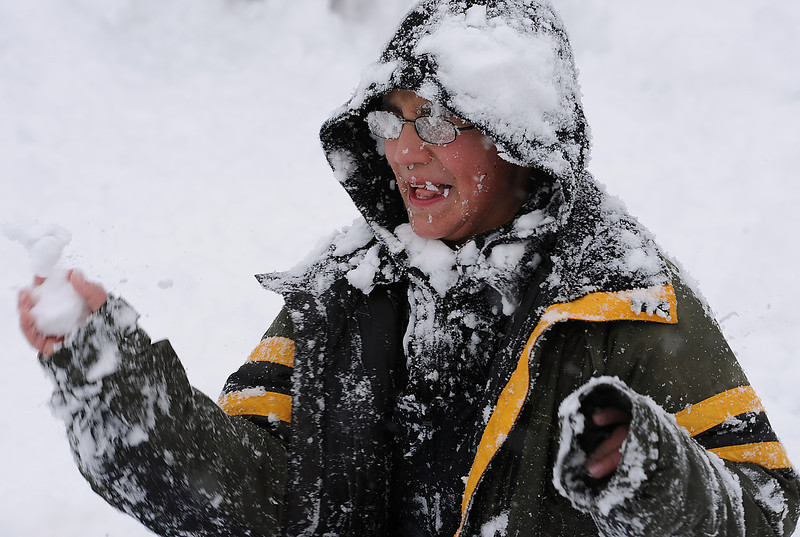 Omar Quintana, 11, has a hard time seeing where to throw a snowball after his glasses were covered in snow Friday while having a snowball fight with friends in Loveland.