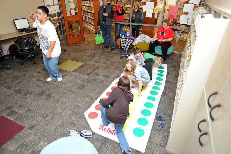 Twelve-year-old Jake Ramos-Wilson, left, looks up at a television screen as he plays along to the video game Dance Central 2 while Dominique Beecher, 7, bottom right, Kadia Odd, 13, Kali Odd, 17, and Abbey Johnson, 5, play a game of Twister in the Mummy Mountain Teen Gaming Room during the grand reopening Saturday, Feb. 18, 2012 of the Loveland Public Library.