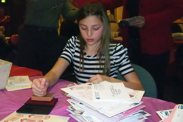 Ten-year-old Hannah Williams stamps a locally designed cachet on valentines Saturday during the Valentine Stamp Camp.