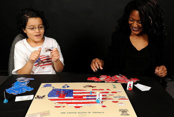 "Tyler Pollard, 12, left, and his mom Sherrin Pollard demonstrate how to play a game called ""Red State Blue State"" Wednesday in Loveland. The two created the game to make it fun and easy for kids and adults to understand the electoral process and American history. Photo by Jenny Sparks"
