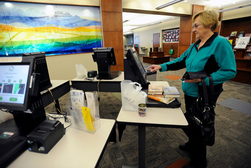 Jan Erickson uses one of the self-checkout stations at the Loveland Public Library to check out several books on Thursday.