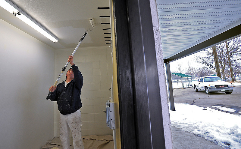 Scott Hansen paints inside the umpire room Friday morning at Barnes Park. Renovations on the building in the center of the complex that houses the concessions stand, restrooms, storage and the umpire room are wrapping up. Photo by Jenny Sparks