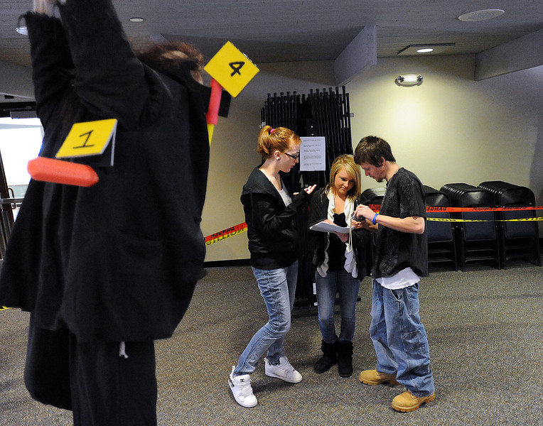 A dummy with a knife in its back and an axe wound in front hangs in the foreground as Ferguson High School students Michaela Luce, 18, left, Casandra Baney, 17, center, and Matt Wells, 18, right, document evidence from a mock crime scene Thursday during a forensoc lab class at the school in Loveland. Photo by Jenny Sparks