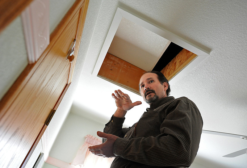 Bruce Pearman with Lightly Treading talks with homeowner John Little, not shown, about the amount of insulation in his attic while performing an energy audit Monday morning at the Little home in Loveland. Photo by Jenny Sparks