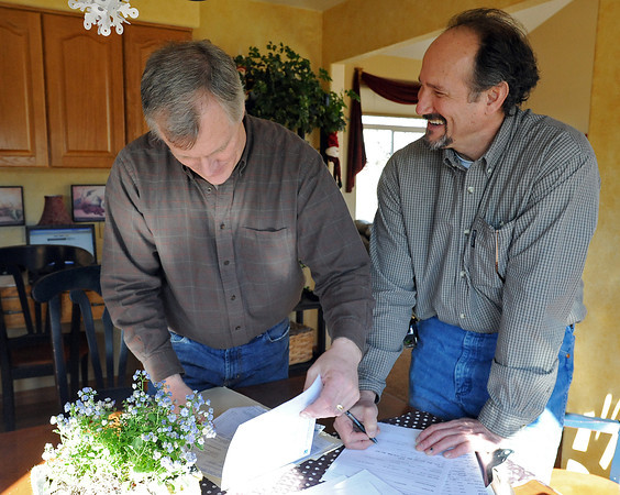 Homeowner John Little, left, shows Bruce Pearman his energy bills Monday as Pearman does an energy audit at Little's Loveland home. Photo by Jenny Sparks
