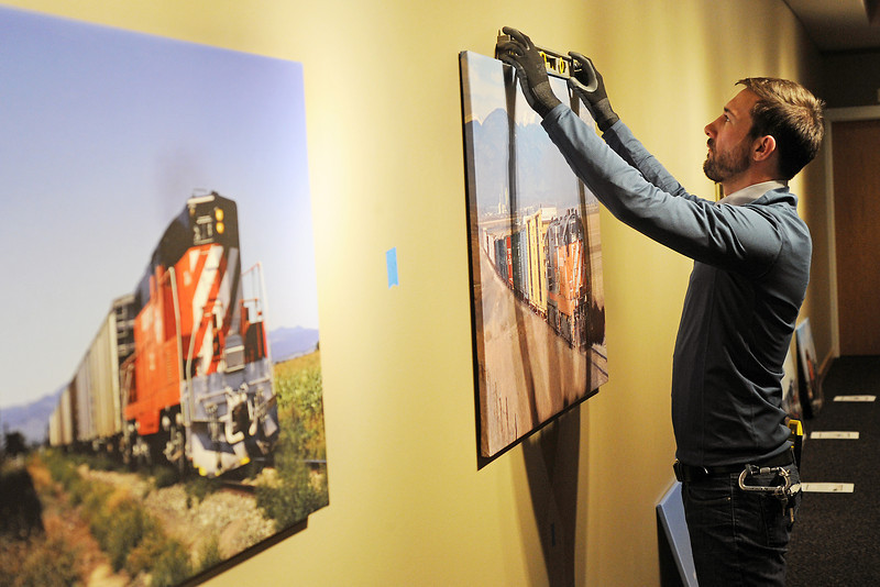"Loveland Museum/Gallery exhibits preparator Quinn Johnson hangs photos Wednesday afternoon in the Foote Gallery that are part of the upcoming display called ""Tracks"" that runs from Feb. 18 to Apr. 15."