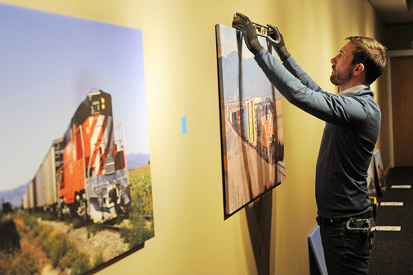 """Loveland Museum/Gallery exhibits preparator Quinn Johnson hangs photos Wednesday afternoon in the Foote Gallery that are part of the upcoming display called """"Tracks"""" that runs from Feb. 18 to Apr. 15."""