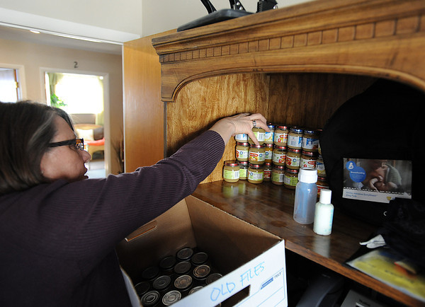 Kathy Roberts, director of Loveland's Life Choices, moves baby food from a shelf Monday while preparing for an open house Thursday. Photo by Jenny Sparks