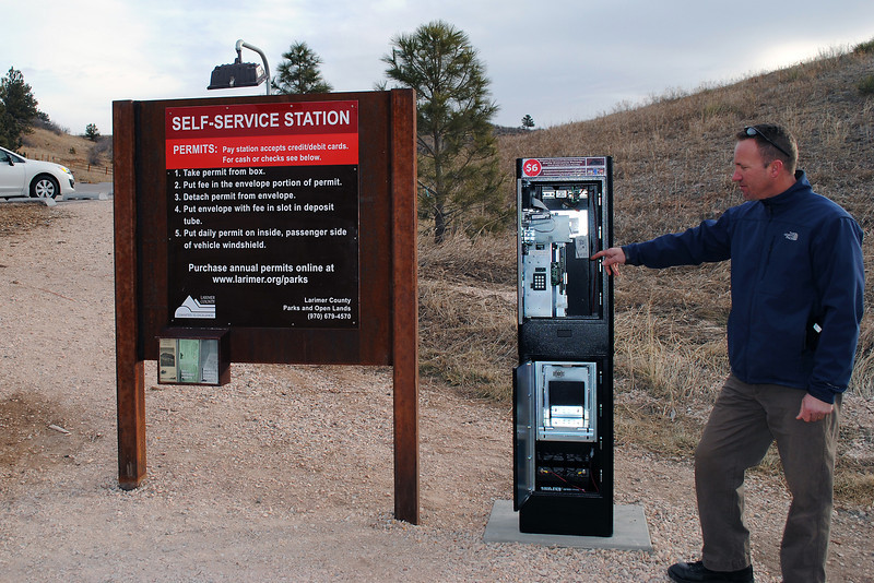 "Natural Resources Manager Travis Rollins shows off a new automated pay station at Horsetooth Mountain Park, which now allows visitors to pay their entrance fees with a debit or credit card. The ""iron ranger"" will sit next to the old fashioned cash or check pay envelopes for six months while county officials study if it follows research that suggests automated systems are more efficient and preferred by visitors."