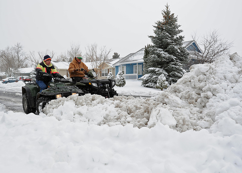 Vic Sheahan, left, and Chuck Hannah use all terrain vehicles to plow snow near their homes on the 1600 block of west 13th Street in Loveland Friday morning.