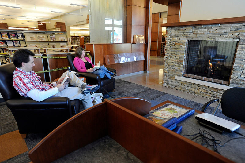 Loveland residents Craig Cable, left, and Holly Cable read together Thursday near the fireplace in the Lillian Colwell Patterson Reading Room in the newly-remodeled Loveland Public Library.