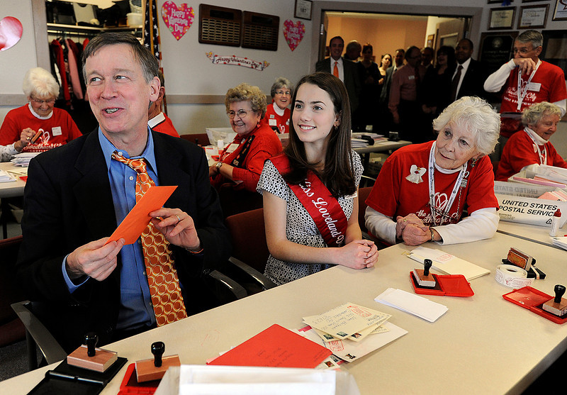 Gov. John Hickenlooper tells volunteers that he just stamped a special Valentine for his wife Thursday at the Loveland Chamber of Commerce. He helped Miss Loveland Valentine Mary Askham, center, long time stamper Joyce Boston, right, and a room full of volunteers stamp Valentines for the Loveland Valentine Re-Mailing Program. Photo by Jenny Sparks/Loveland Reporter-Herald