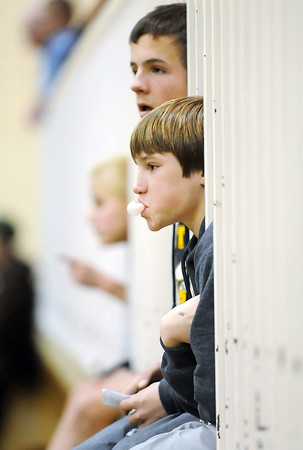 Walt Clark Middle School seventh graders Parker Simington, 12, front, and Gunner Mengel, 13, poke their heads and bodies through a handrail as they watch the Class 4A Region 3 Wrestling Tournament on Friday, Feb. 11, 2011 at Thompson Valley High School.