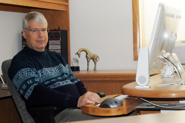 Loveland-based author Mike Stauder, who has been writing for 15 years and has seven self-published novels, poses Thursday in his home office.