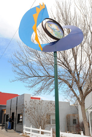 """Loveland resident Martin Kelly enters the Loveland Small Business Development Center, 441 E. Fourth St., Suite 101A, near the sculpture """"Uncomplicated Moon"""" by, Reven Swanson which is one of the temporary pieces in The Art Advocacy Program."""