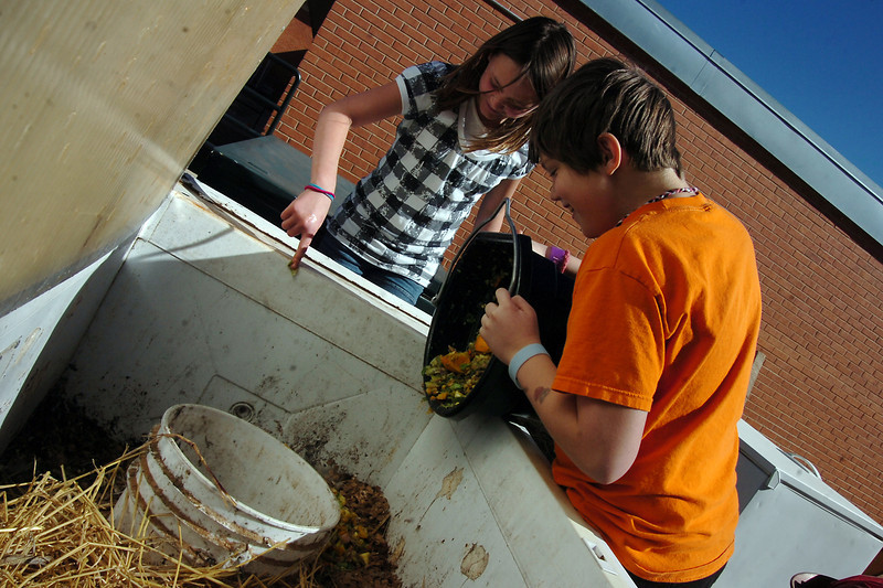Big Thompson Elementary School fifth graders Rylee Burton, 10, left, and Seth Keck, 11, dump food scraps they collected over the lunch period into a worm bin located outside the school. The two worm wranglers collected more than 20 pounds of scraps for the bin.