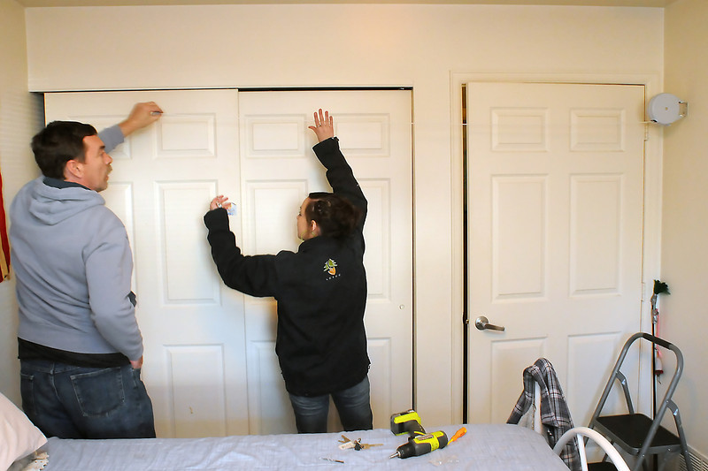 Cliff Carlstrom, left, assists Larimer County Youth Conservation Corps member Cassandra Leverette as she installs a retractable clothesline in a bedroom of Donna Sisson's apartment in Loveland on Friday.