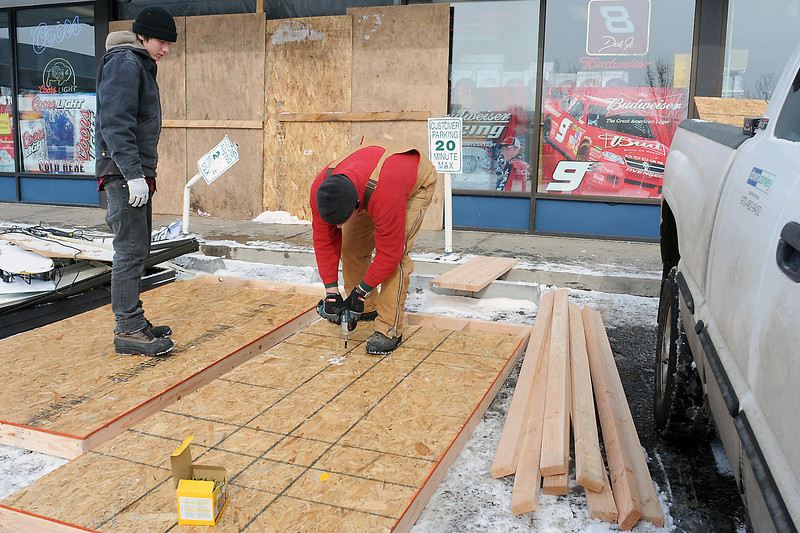 Down Zankey Construction Inc. owner Jeff Down, right, and his son, Sidney Down, build temporary walls to outside Countryside Liquor, 109 E. 37th St. on Tuesday morning to patch a hole that was caused Monday night when a car crashed into the building.
