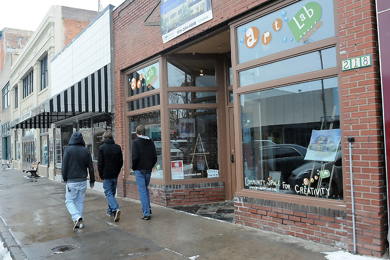 Loveland residents Dillon Cole, left, Jacob Morey and Bryan Stevens walk past Art Lab and the former Quality Shoe Repair on East Fourth Street in downtown after having coffee together at Mandolin Cafe, 210 E. Fourth St. on Thursday afternoon.