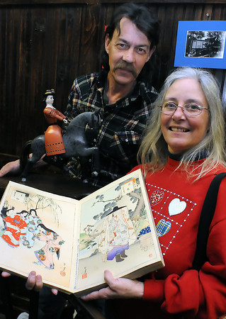 Longmont residents Dave and Kim Hall pose Saturday while holding a wooden Norwegian horse and Japanese print book that they brought in to be appraised during the Berthoud Historical Society's Antique Appraisal Day on Saturday at the Little Thompson Valley Pioneer Museum.