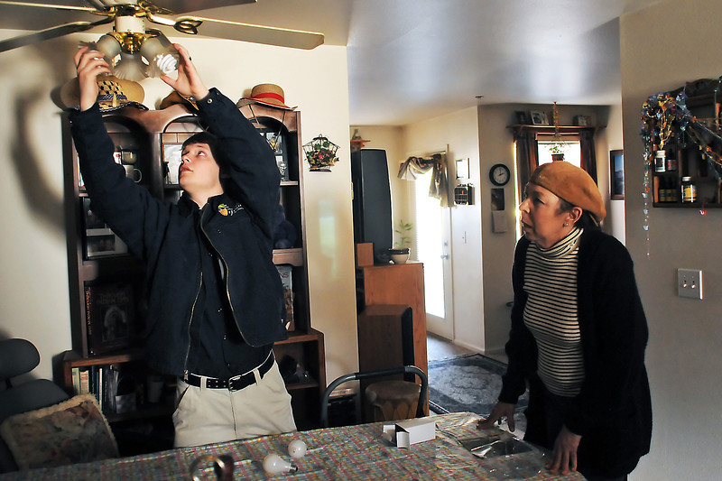 Donna Sisson, right, watches as Larimer County Youth Conservation Corps member Will Wright installs a compact flourescent lightbulb in her apartment Friday during an energy audit by the volunteer group.