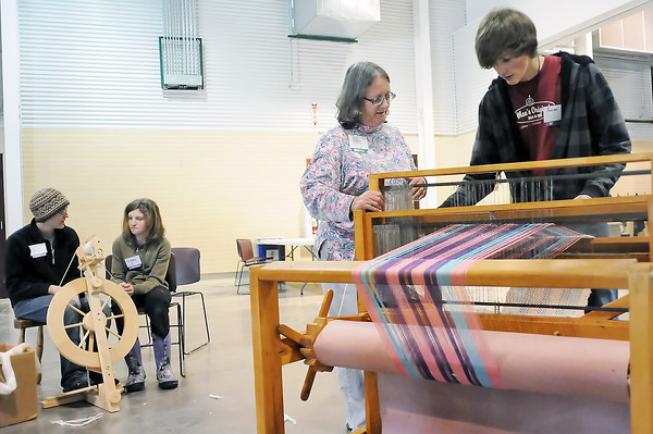 Aaron Armstrong, 15, right, learns how Susan Epperson's 4-harness loom works while Erin Epperson, back left, teaches Sidney Callahan, 13, the process of spinning yarn on a spindle during the Fiber Fun Fest on Saturday at The Ranch.