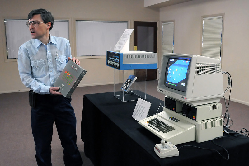 Loveland resident David Charles holds a copy of VisiCalc, which was the first spreadsheet program for personal computers, as he talks about some of the computers and related items contained in the Colorado Computer Museum's collection on Friday at Galilee Baptist Church, 2525 Van Buren Ave. At rear is an Altair 8800 personal microcomputer from 1975 and at right is an Apple II Plus home computer which was introduced in 1977.