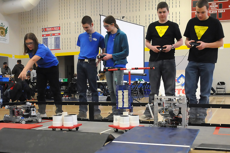 "Participants in the First Tech Challenge Northern Colorado Scrimmage run their robots on the field on Saturday at Kinard Middle School in Fort Collins. From left are Jennifer Malone, 17, Christopher Dyer, 15, and Kira Lindburg, 16, of Poudre High School's ""Alpine Robotics"" team and Ethan Rogers, 14, and T.J. Willecke, 16, who are home schooled and on team ""Byte Riders."""