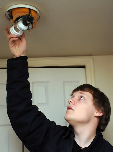Larimer County Youth Conservation Corps member Will Wright installs a compact flourescent lightbulb in a hallway fixture in Loveland resident Donna Sisson's apartment Friday during an energy audit by the volunteer group.