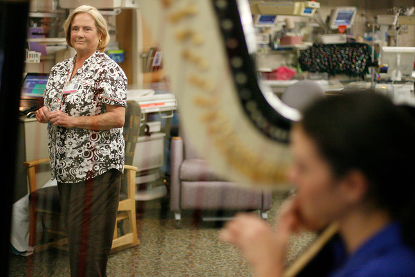 Laurie Bacheller, RNC, watches as Hillary Schefter plays the harp in the Neo Natal Intensive Care Unit on Friday at St. Joseph's in Denver. Bacheller was Schefter's nurse in the NICU 25 years ago.  (Photo by Gabriel Christus)