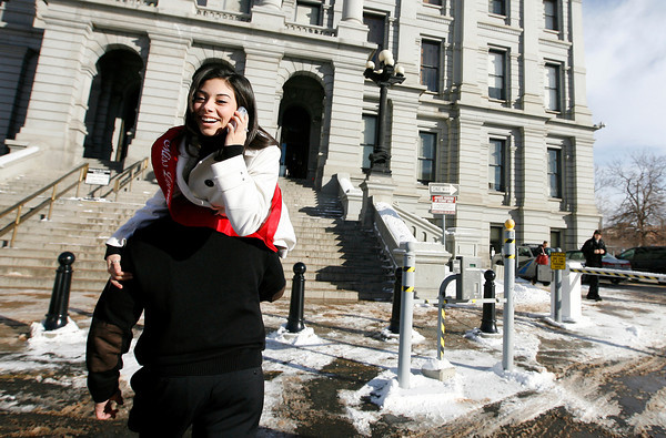 Mike Felton, the father of Miss Loveland Valentine, Jamie Felton, carries his daughter from the limo to the steps of the State Capitol on Monday morning in Denver. Photo by Gabriel Christus