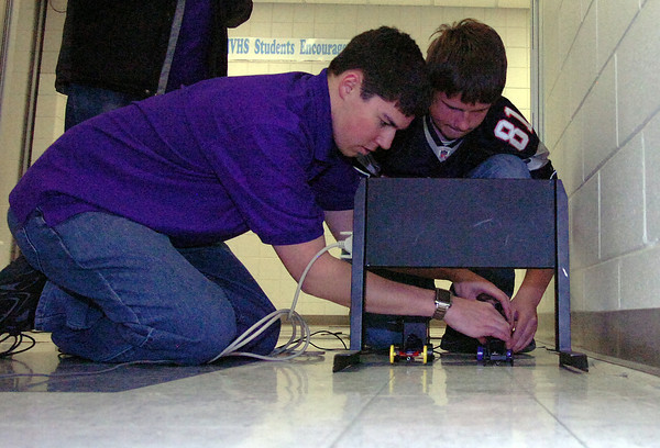 Students Michael Bloom, left, and Jordan Johns prepare to test CO2 cars Tuesday. Bloom won first place in hydrodynamics and elastic powered vehicles.
