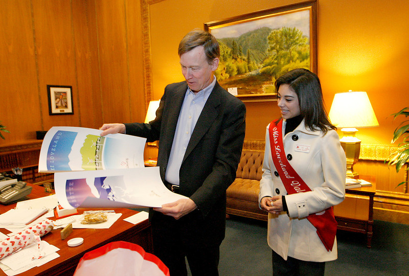 Governor Hickenlooper looks over some gifts that Miss Loveland Valentine, Jamie Felton gave him on a tour of the State Capitol on Monday in Denver. Monday was also the Governor's birthday. Photo by Gabriel Christus