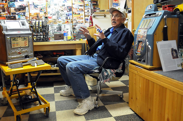 Berthoud resident C.R. Svendsen sits in his home workshop surrounded by several antique slot machines as he talks Fridya about how he repairs and restores the machines.