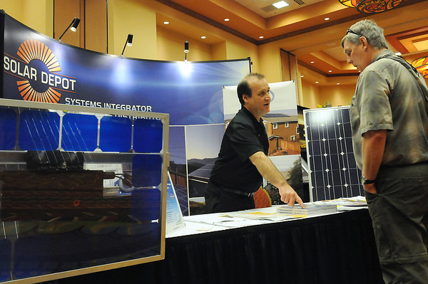 Solar Depot marketing manager Justin Mizany, left, chats with Lakewood resident Chuck Welle during the Colorado Solar Energy Industries' Solar Expo on Thursday at the Embassy Suites Conference Center.