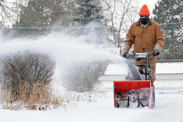 Loveland resident Rodney Hansen uses a snow blower to clear his driveway Tuesday morning in the 2200 block of North Garfield Avenue.