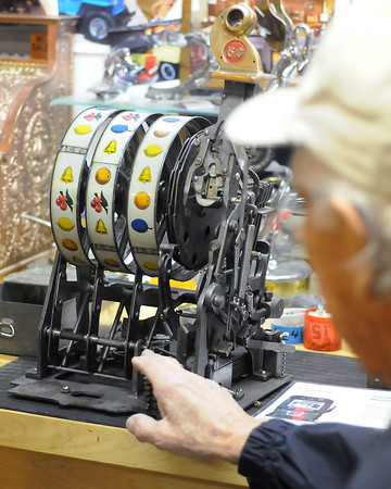C.R. Svendsen talks Friday about the inner workings of a vintage slot machine that he has disassembled and is in the process of restoring.
